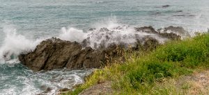 Het water beukt op de rotsen
