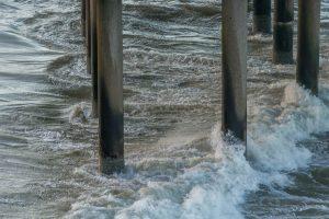 De golven klotsen tegen de pilaren